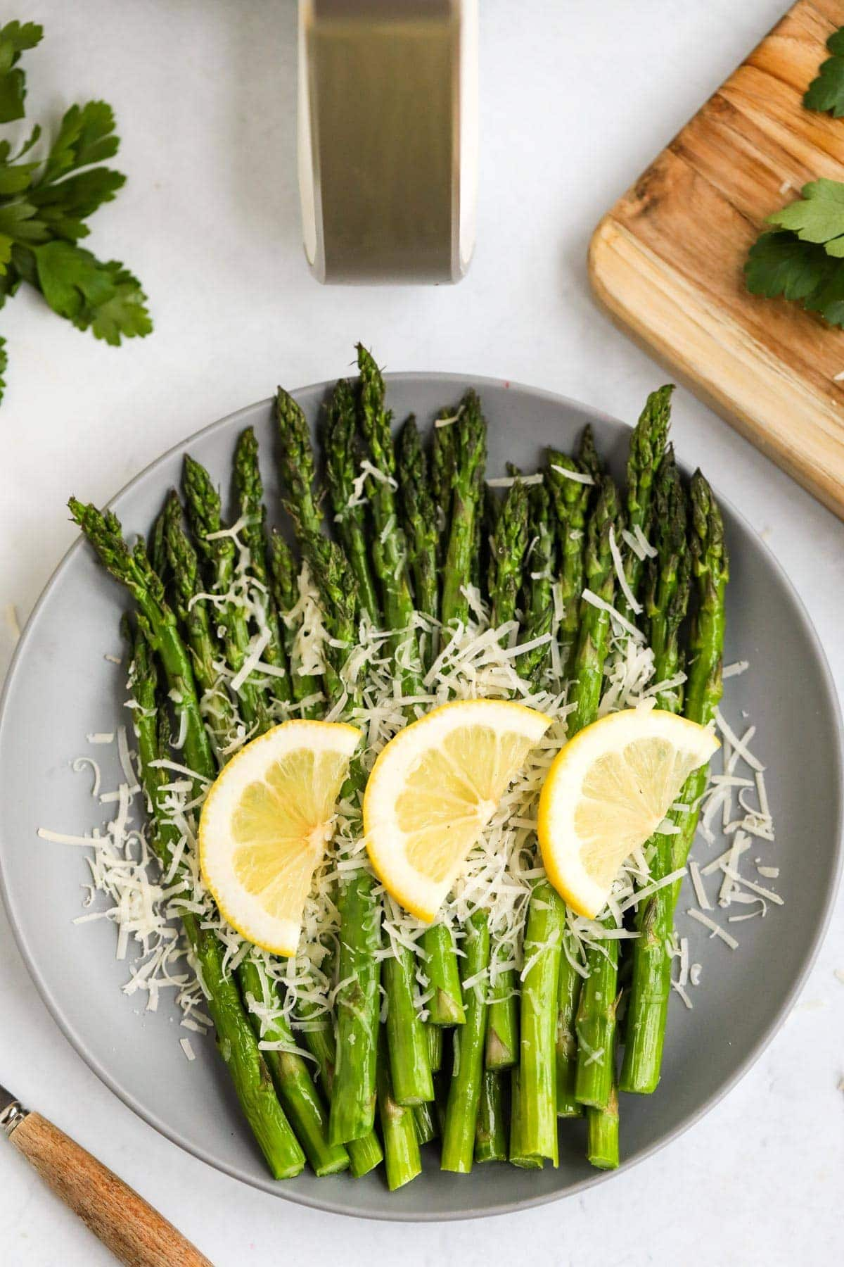 white plate, asparagus with lemon slices and parmesan, wood cutting board, air fryer handle