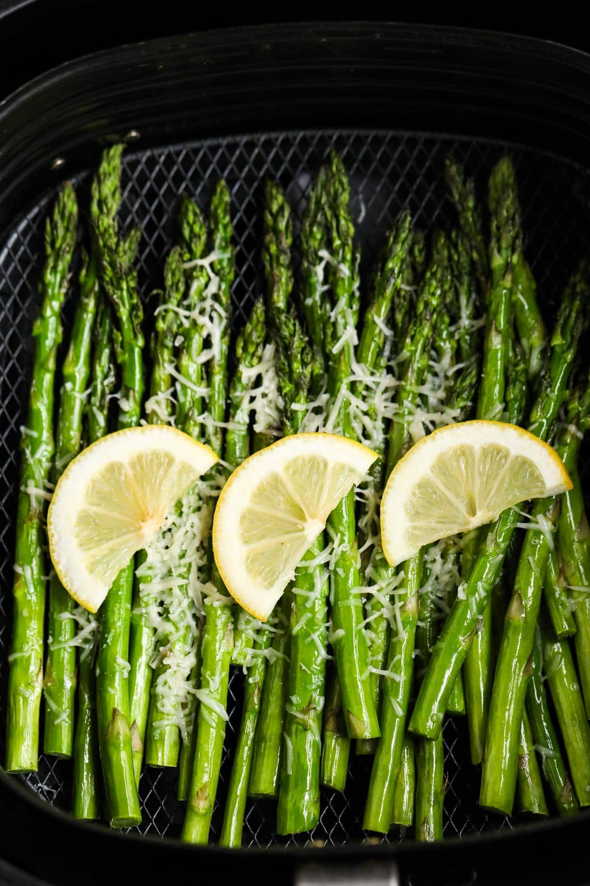 asparagus in air fryer basket with lemon slices and parmesan cheese