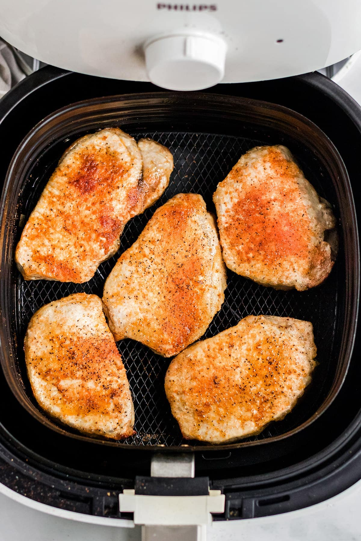 air fryer with pork chops in the basket