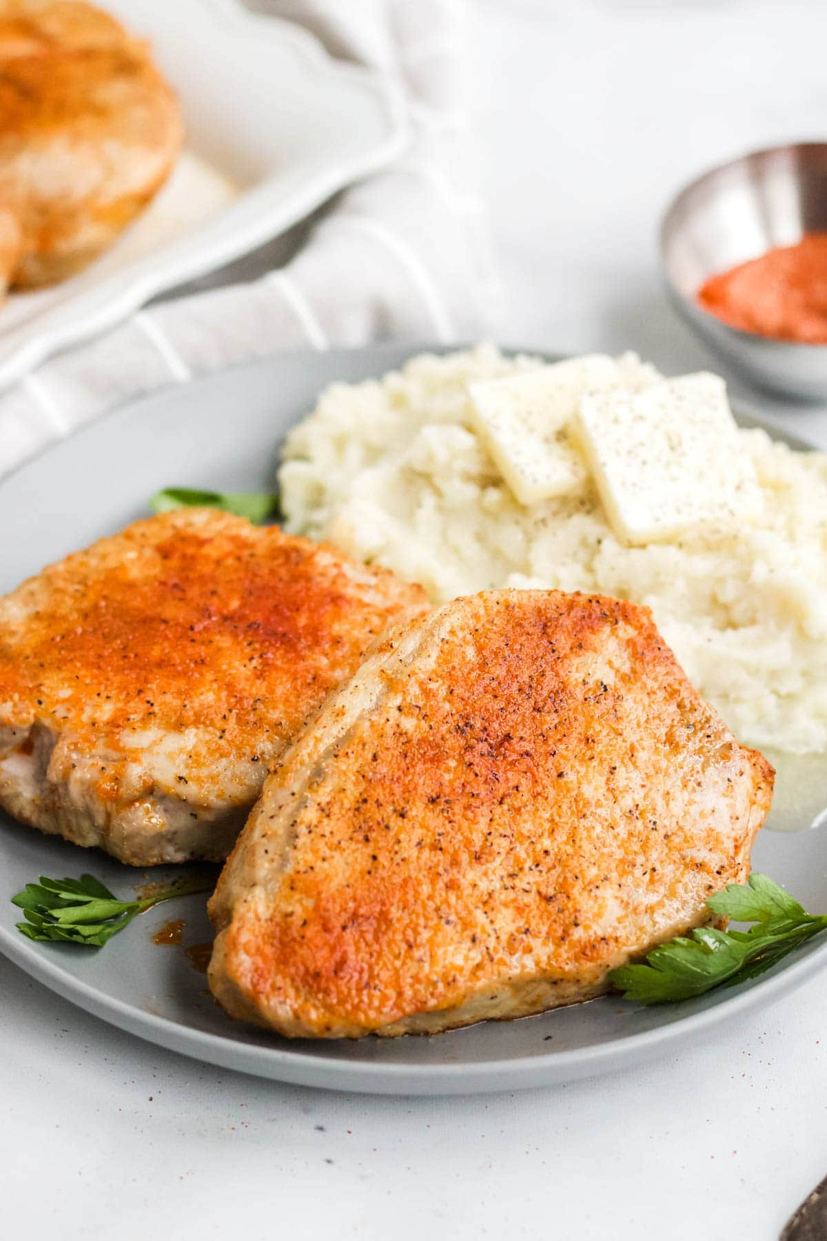 plate with mashed potatoes, pork chops and parsley