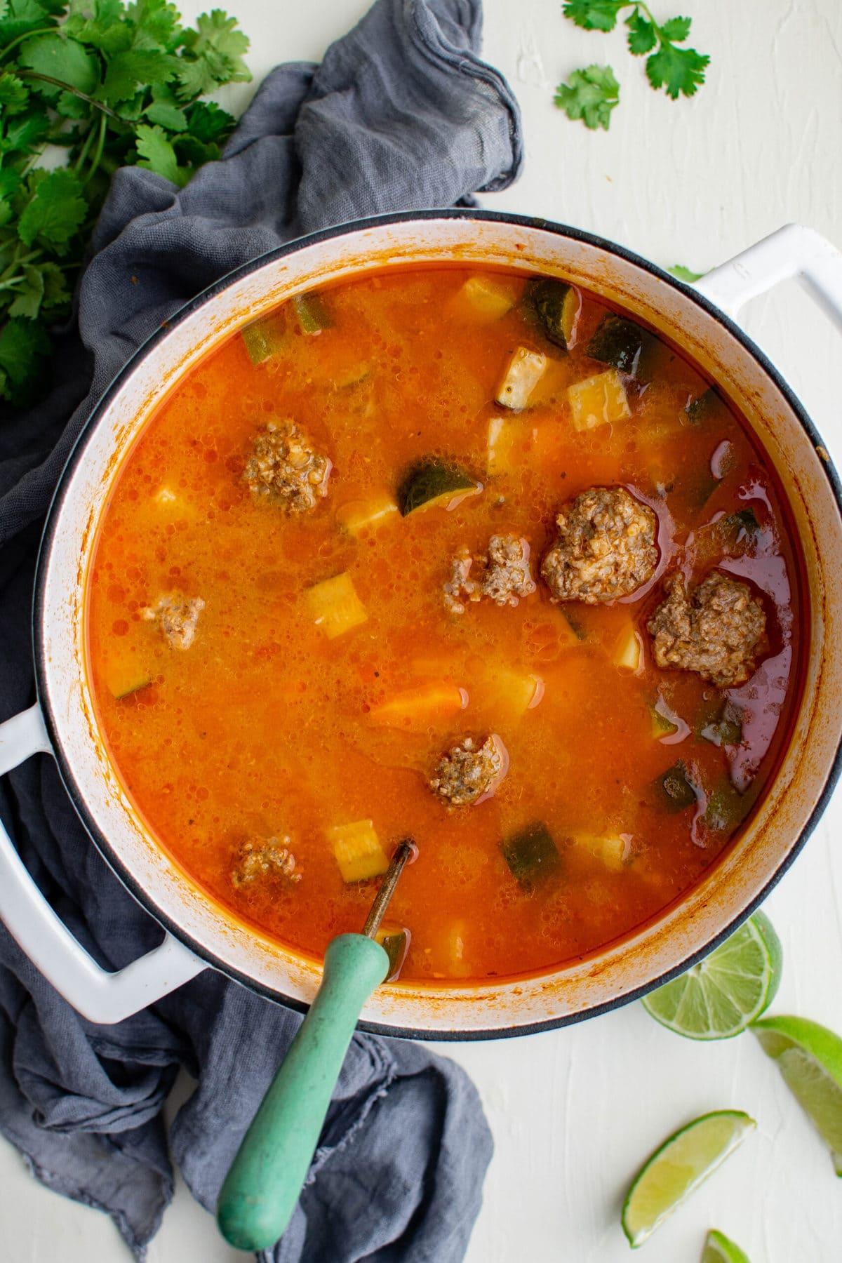 white soup pot, ladle, blue napkin, cilantro, limes, albondigas soup