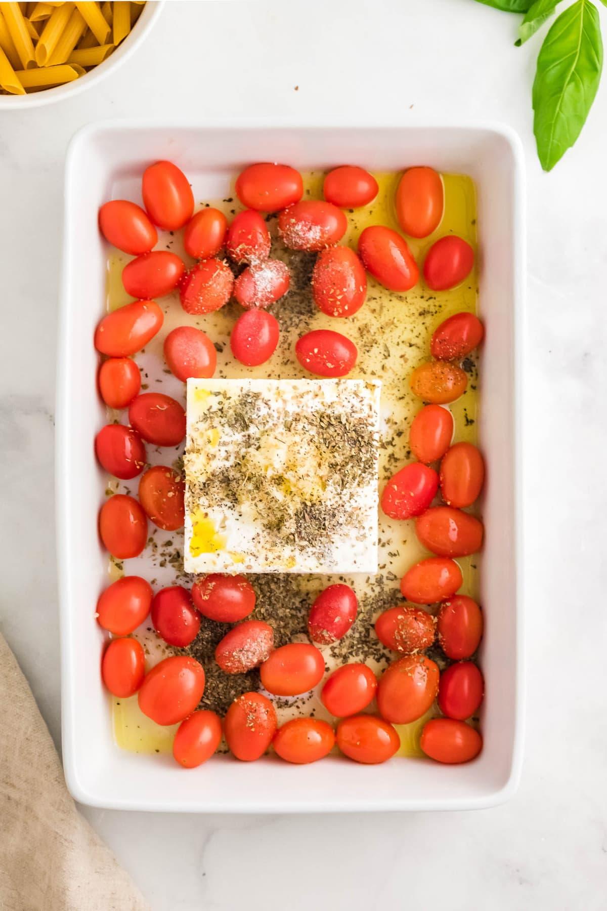 white baking dish, tomatoes, olive oil, block of feta, italian seasonings, pasta, basil