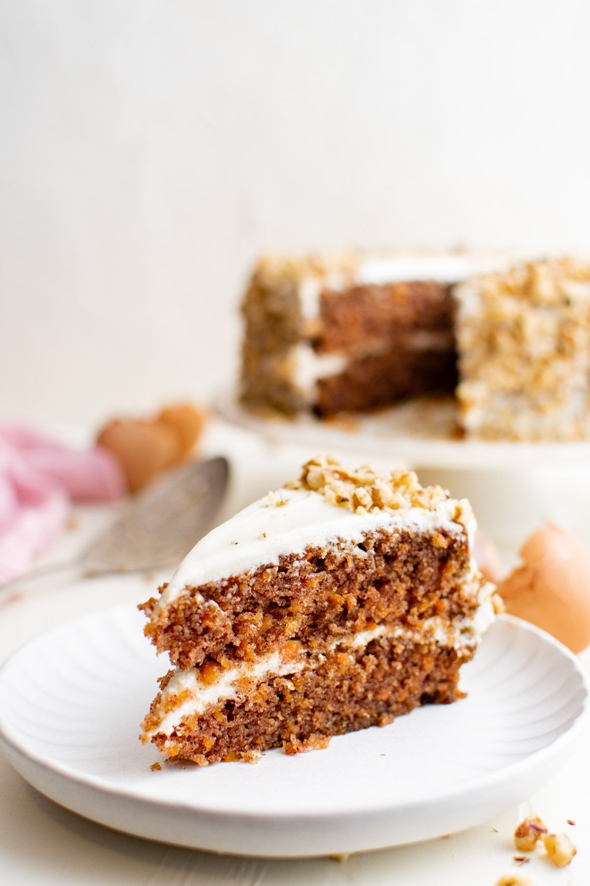 slice of carrot cake on a white plate, whole cake in the background