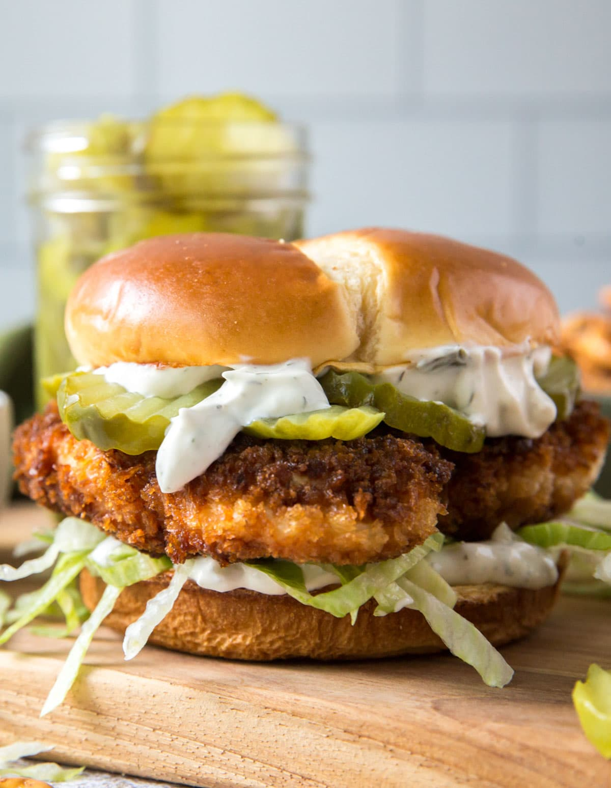fried chicken sandwich with lettuce and pickles on a bin, wood cutting board, jar of pickles