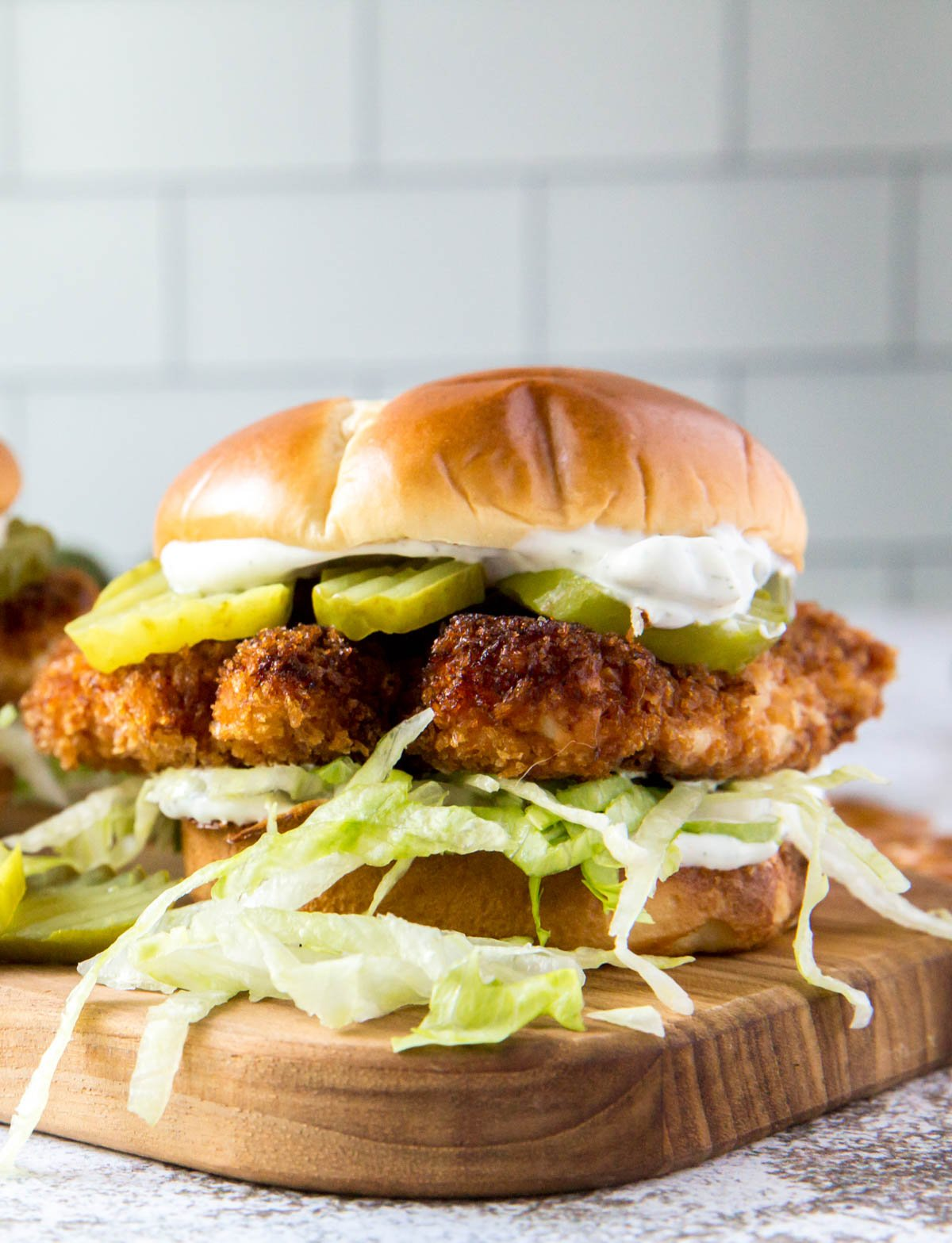 a crispy chicken sandwich with letttuce on a bun on top of a wood cutting board with pickles