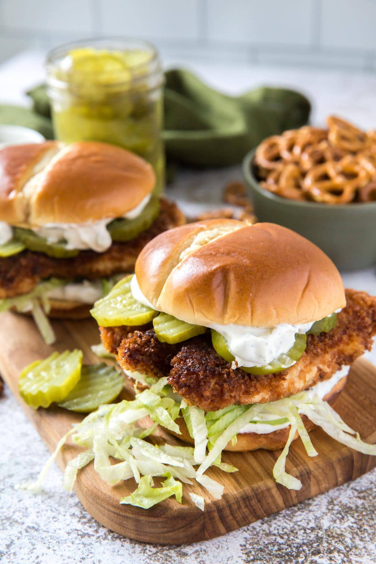 crispy chicken sandwiches on a wood board with lettuce and pickles, bowl of pretels
