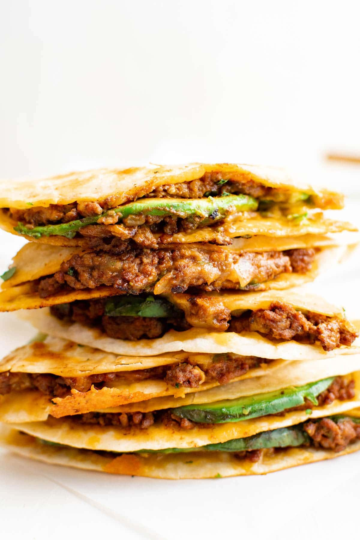 stack of ground beef quesadillas with avocado