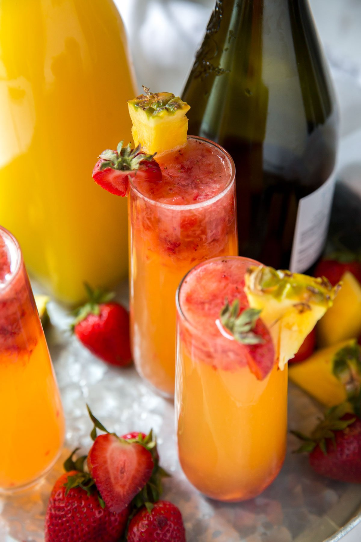 champagne glasses with pineapple juice and strawberries, bottle of champagne