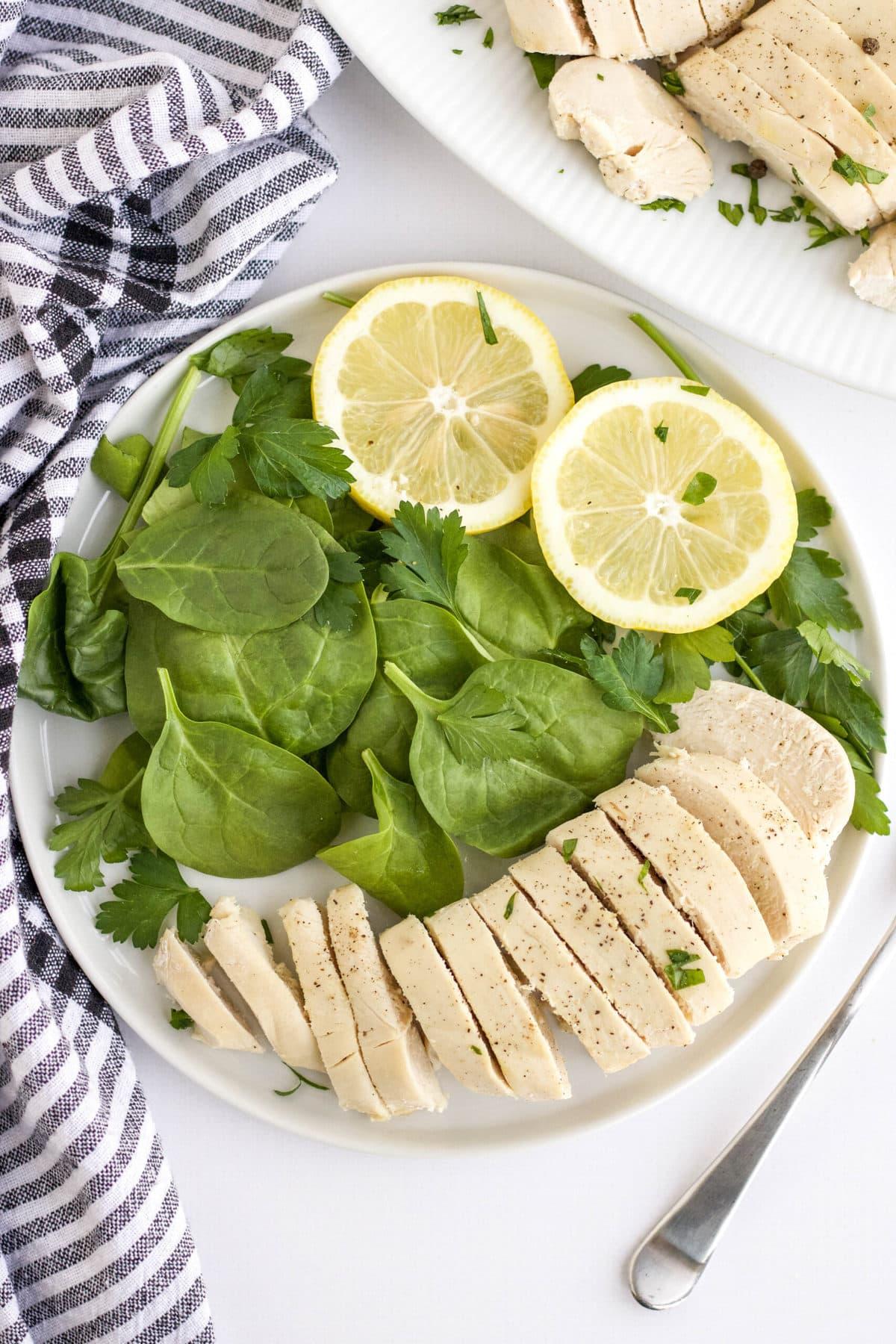 sliced chicken, salad, lemons, blue and white striped napkin