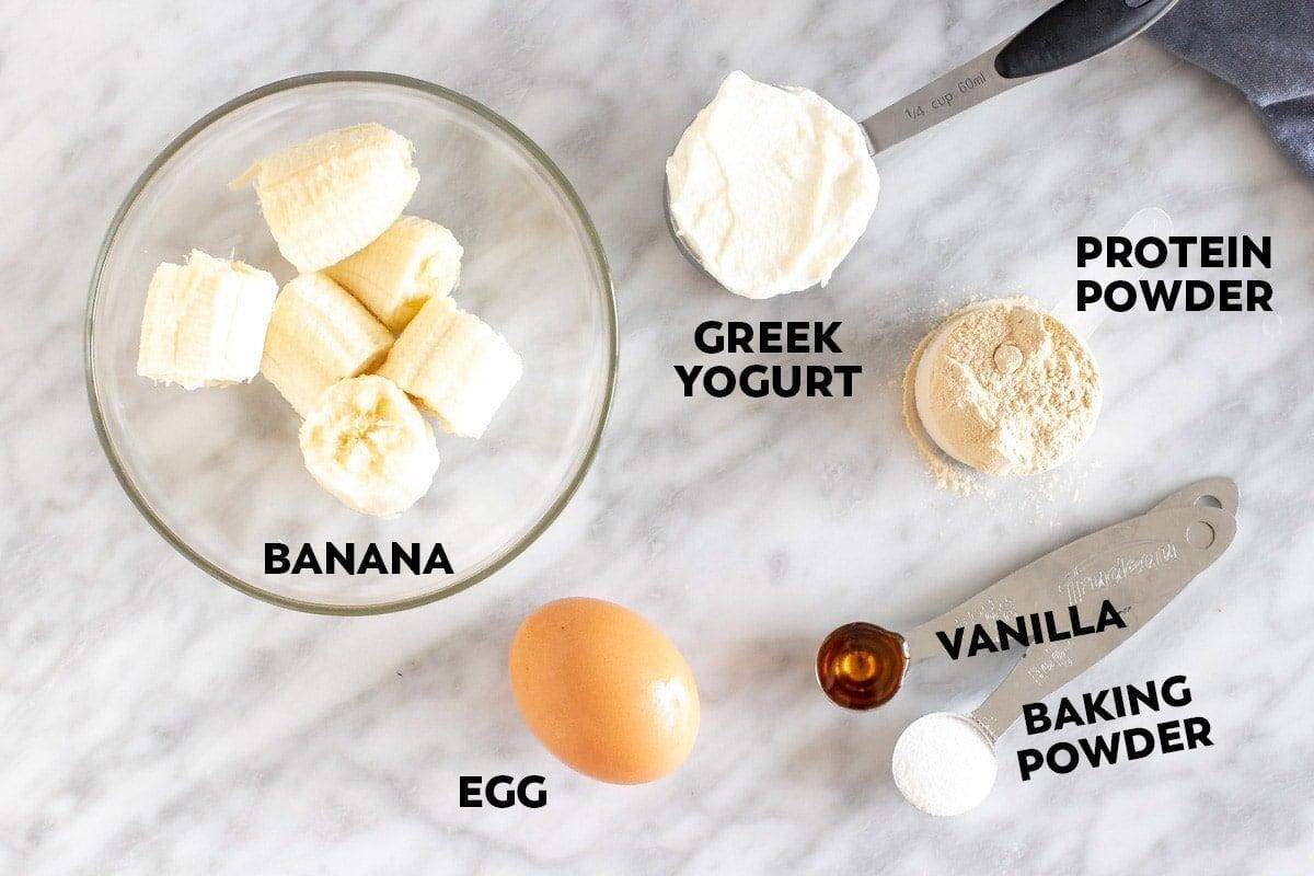 banana in a bowl, an egg, cup of greek yogurt, teaspoons of vanilla and baking powder
