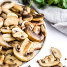 Sauteed Mushrooms on a white plate with herbs in the background.