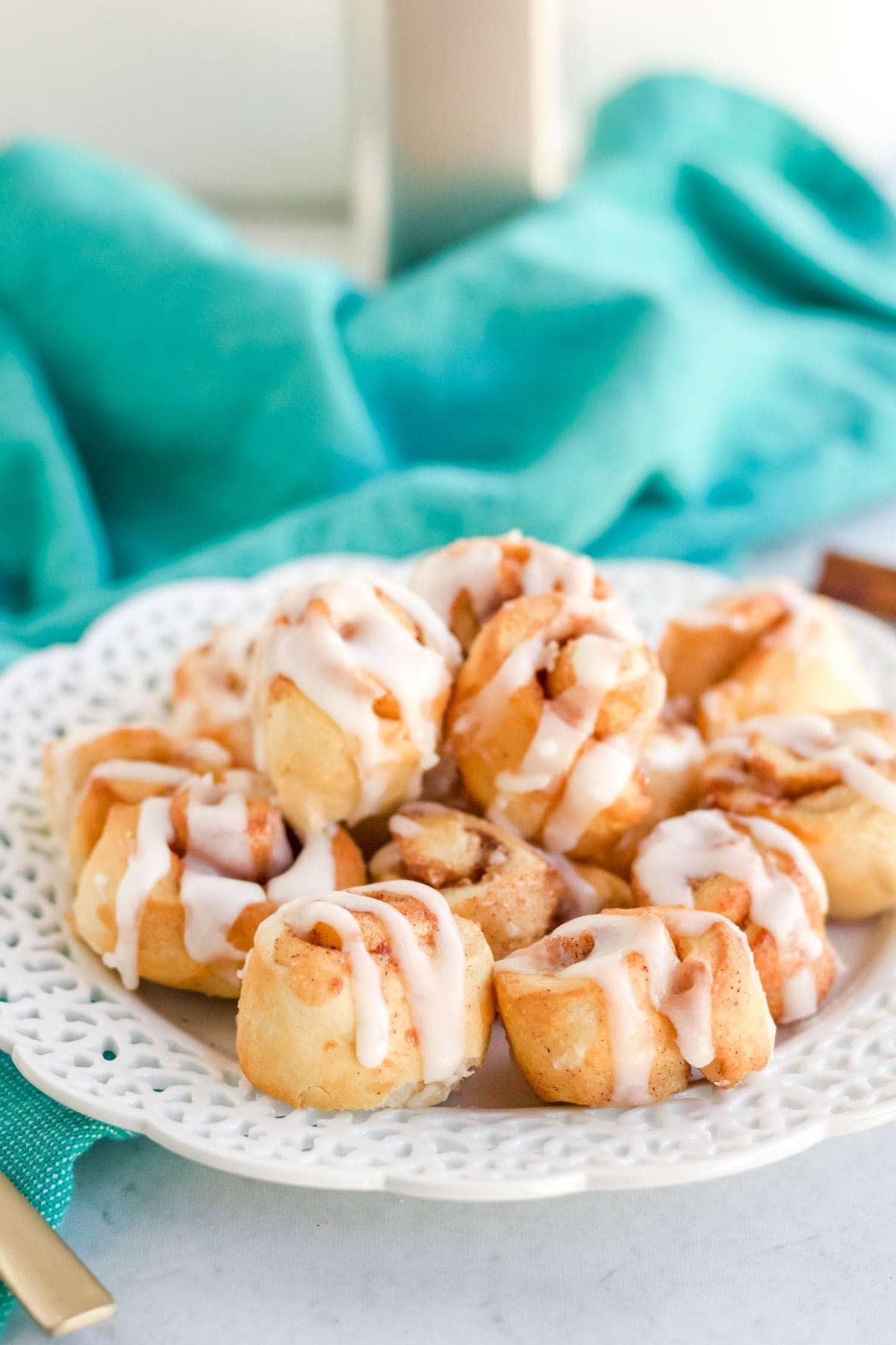 mini cinnamon rolls on a white platter, blue towel, air fryer