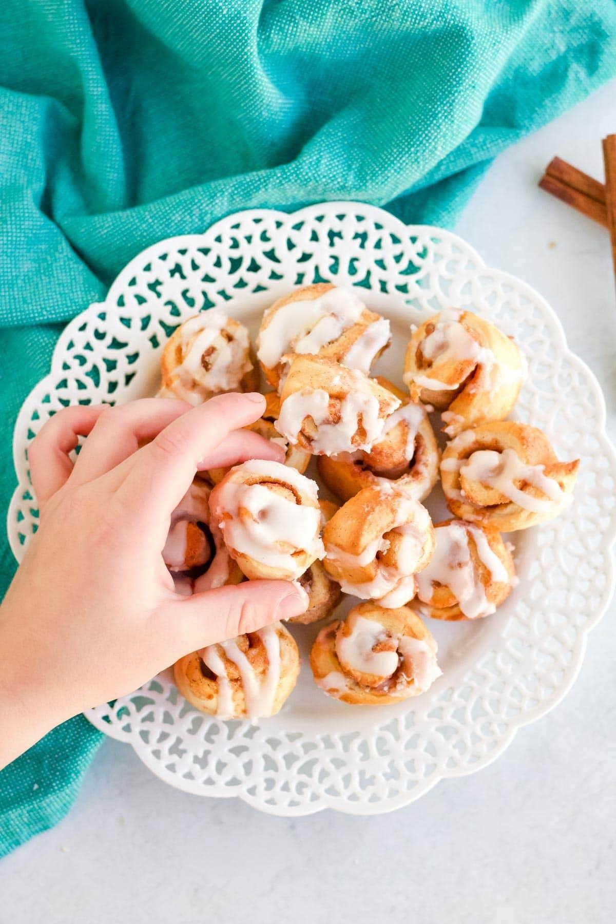 blue napkin, white lacy platter, hand reaching for mini cinnamon rolls