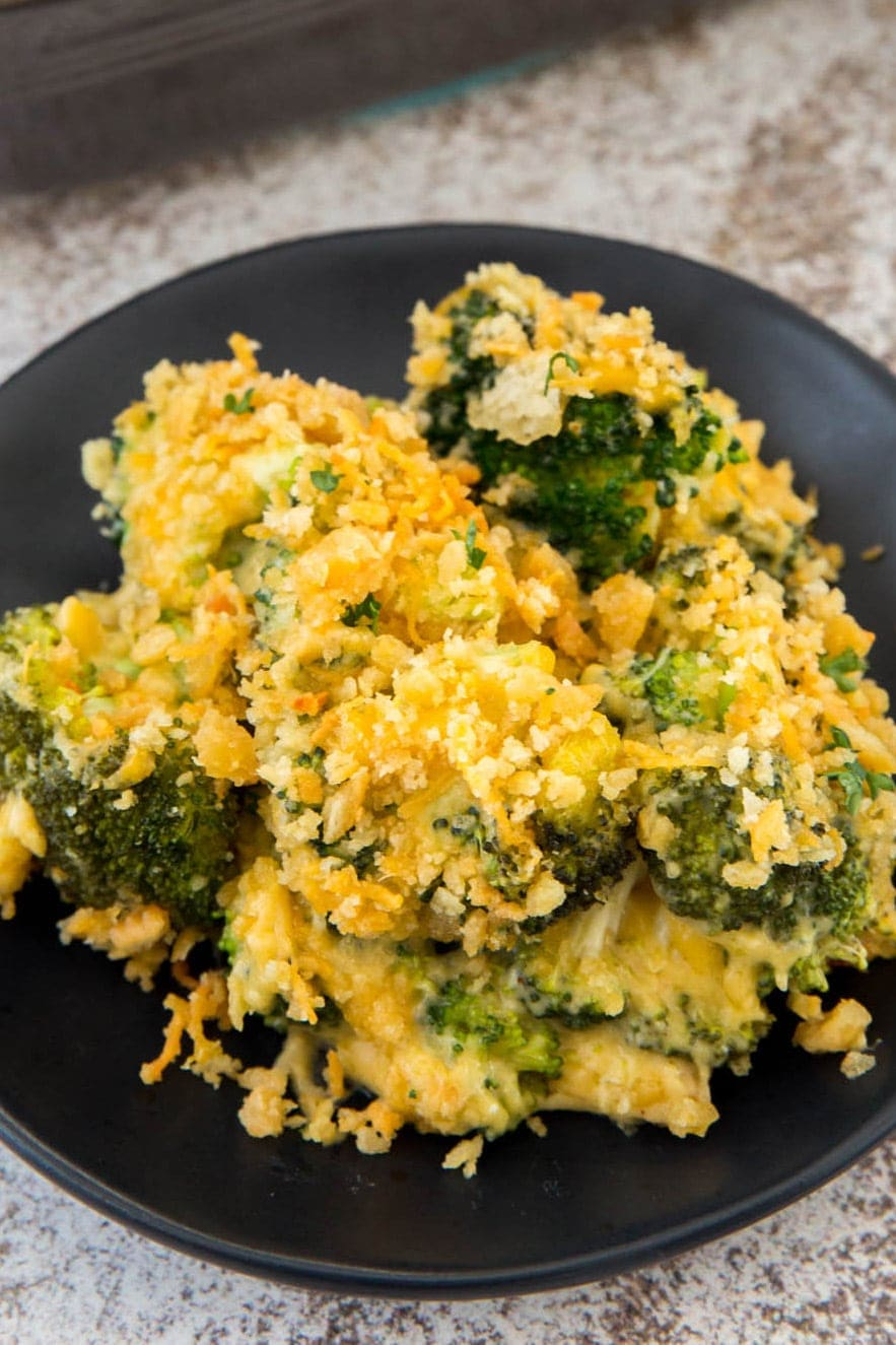 broccoli with cheese sauce and cracker topping on a black plate