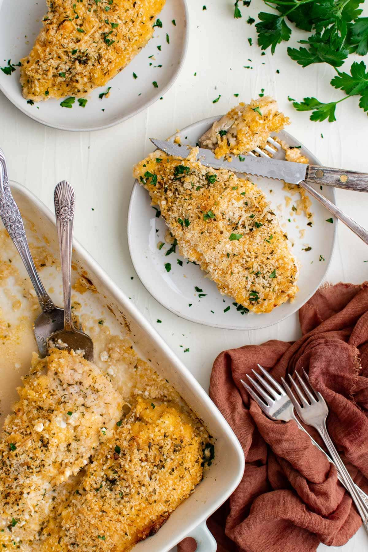 baking dish, chicken breasts with breadcrumb topping, pink napkin, forks, parsley, white plates