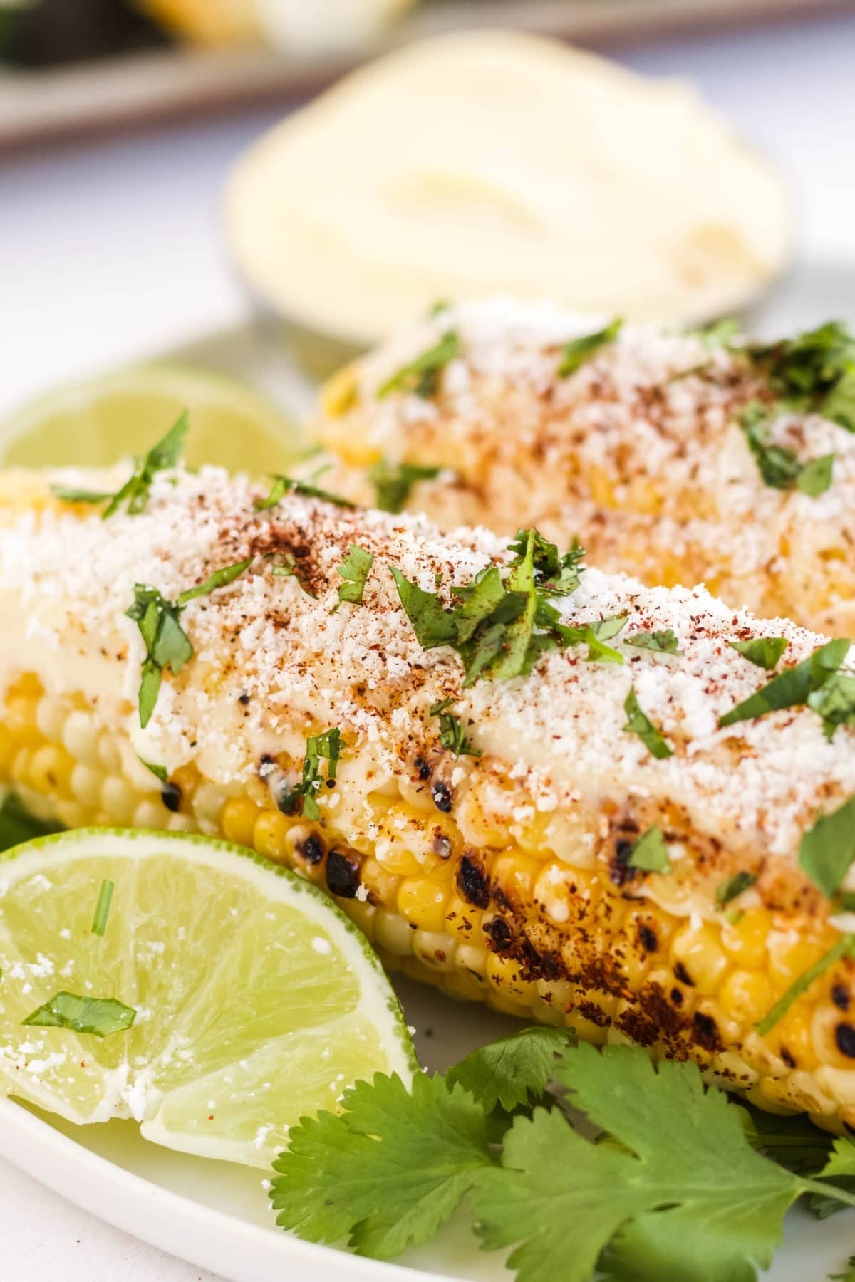 corn on the cob with cheese, cilantro and lime on a plate