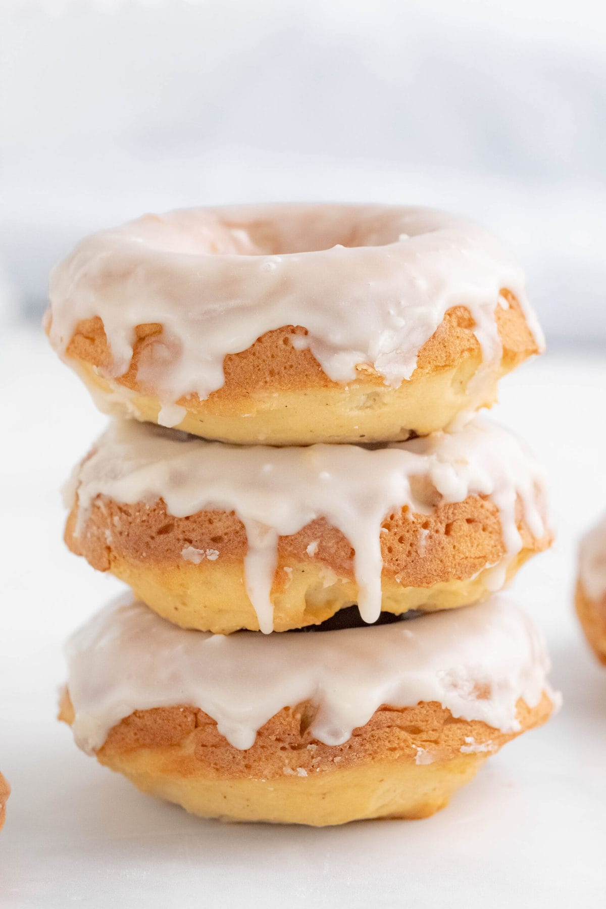 stack of three baked donuts with white glaze dripping down the sides