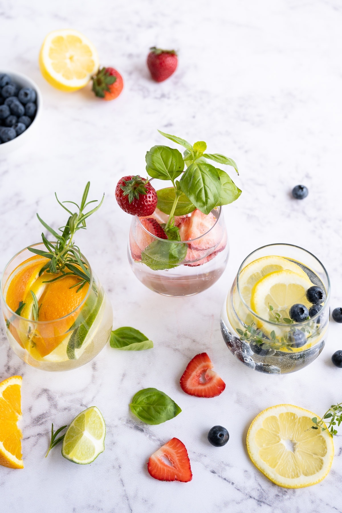 Three glasses with infused water in three glasses with strawberries, citrus fruit, fresh herbs, and blueberries.