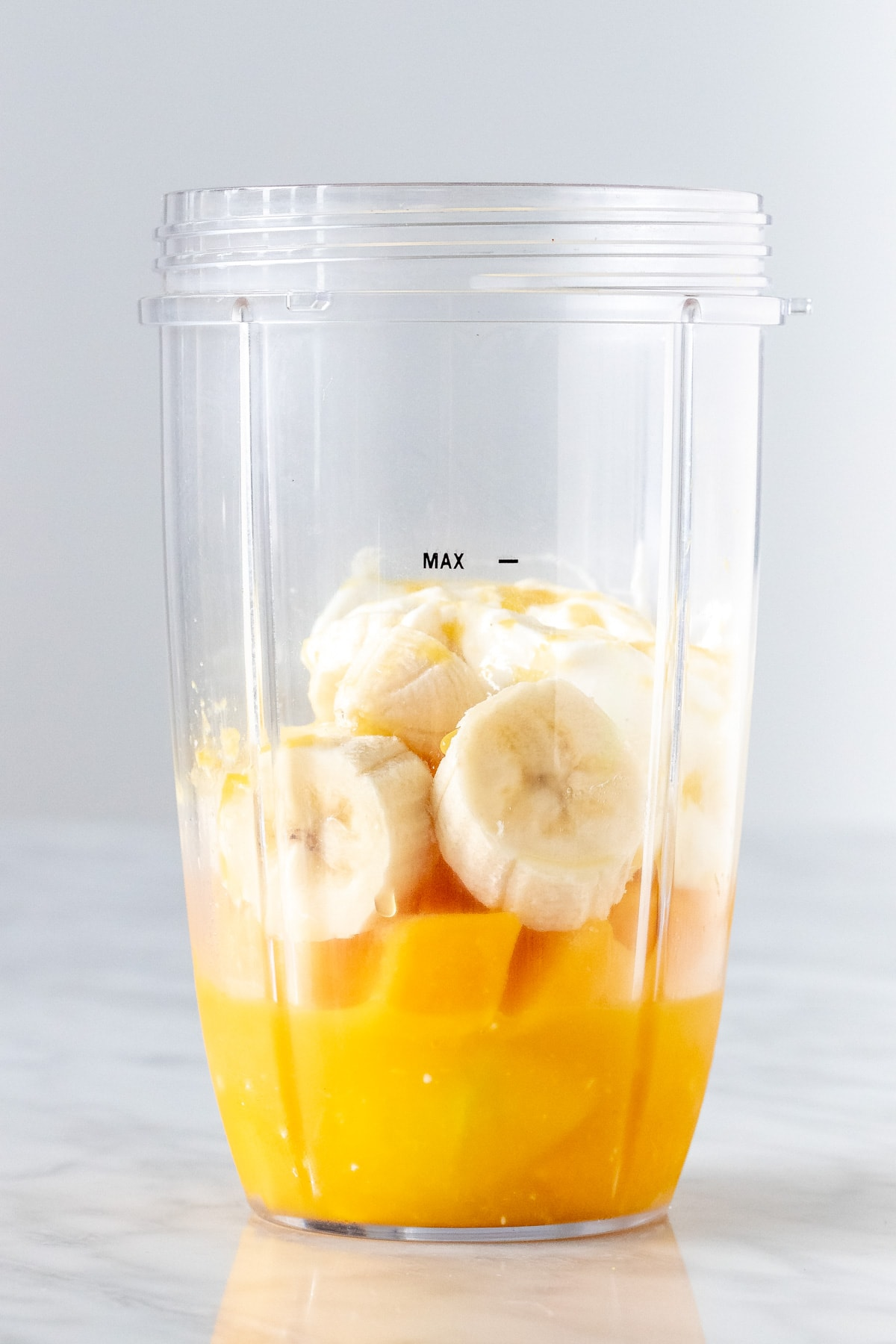 Blender CONTAINER WITH ORANGE JUICE, MANGO AND BANANA