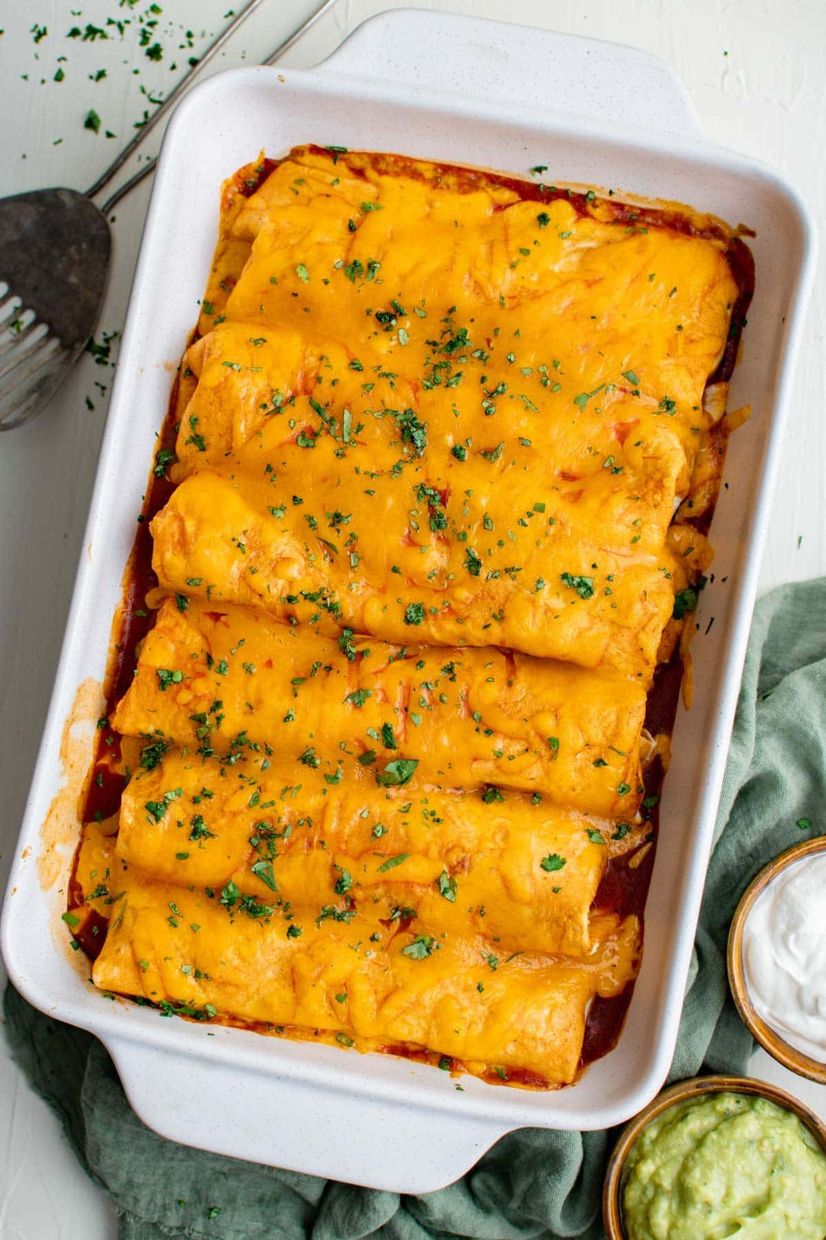 smothered wet burritos arranged in a large baking dish