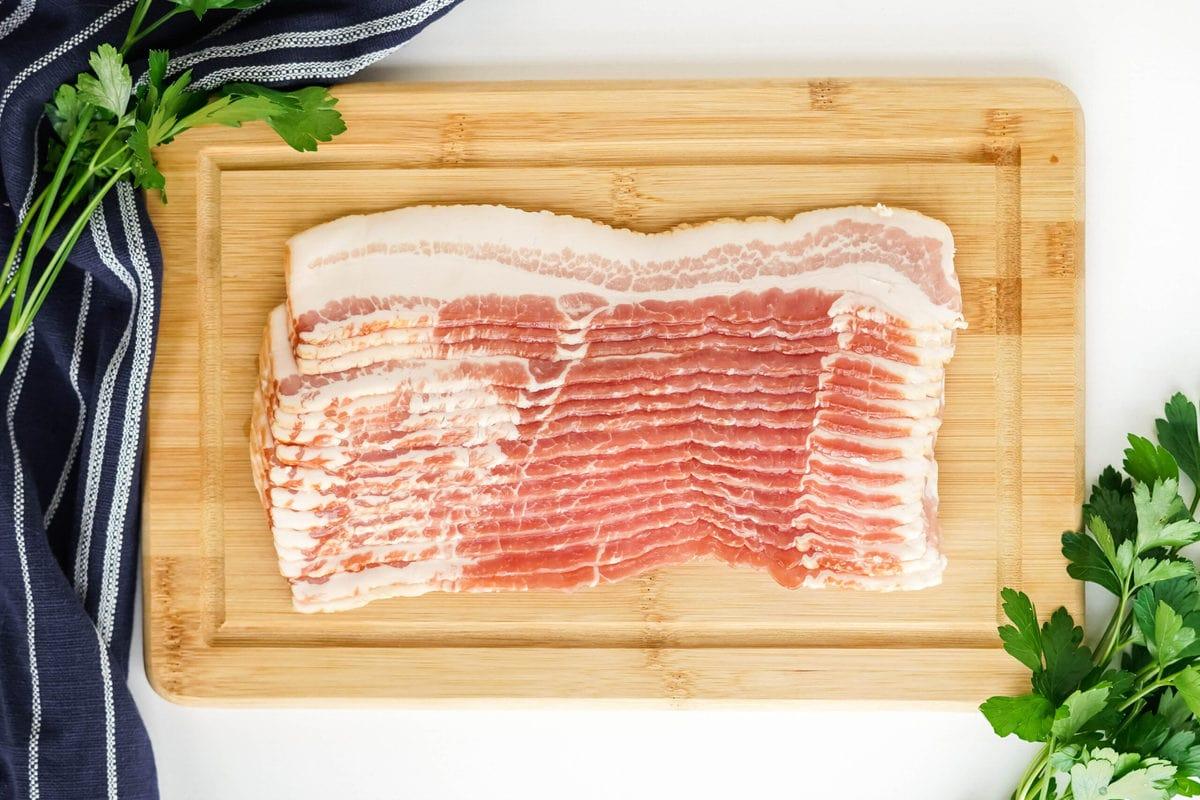 raw bacon on wood board