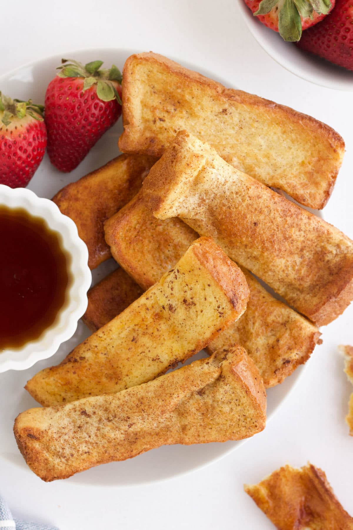 french toast on a white plate, small dish of syrup, strawberries