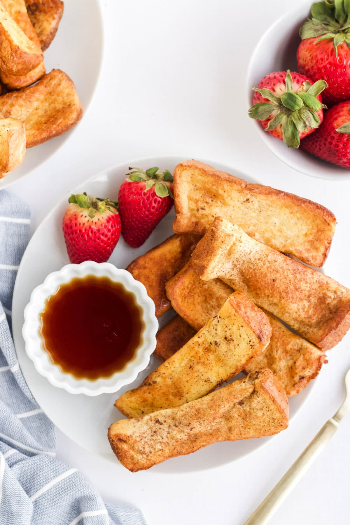 sticks of french on white plate, strawberries dish of syrup