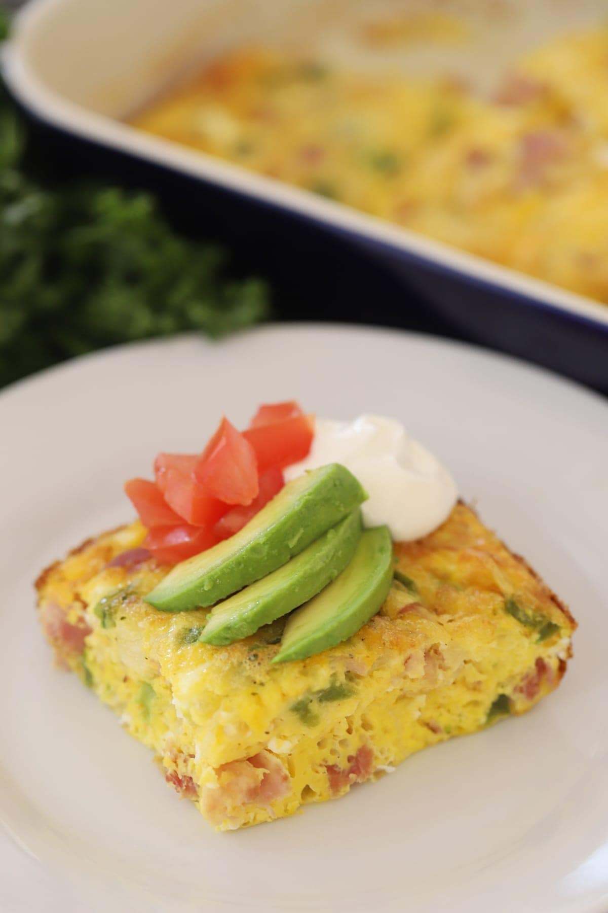 Baked Denver Omelet on a white plate, covered in sour cream, diced tomatoes and sliced avocado