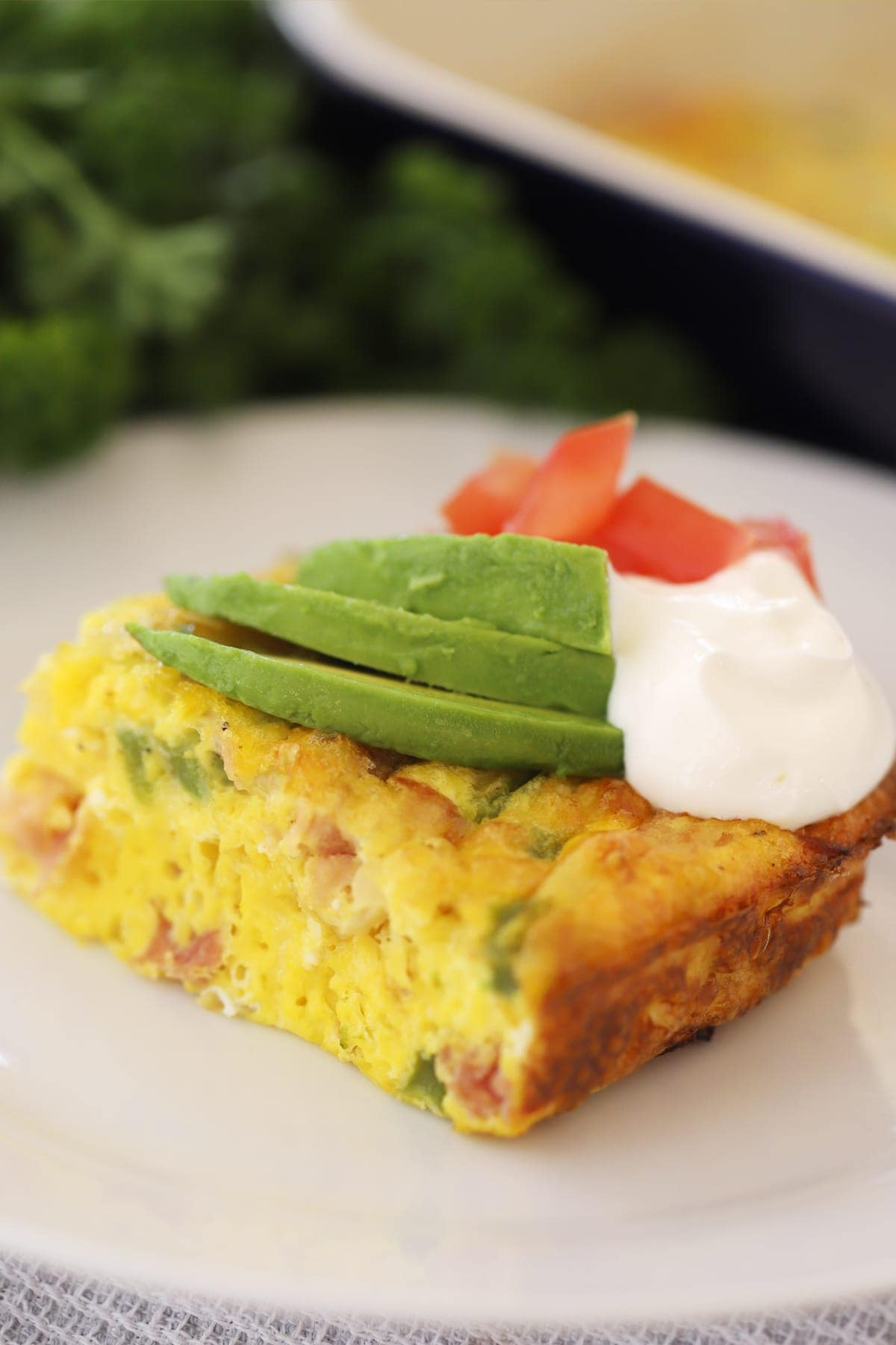 a square piece of a baked Denver omelet on a white plate