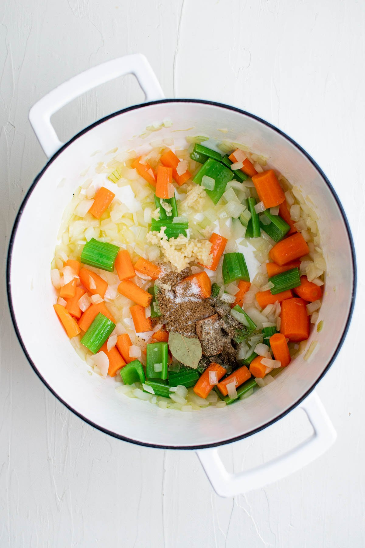 white dutch oven with carrots, celery, onions, bay leave and other spices