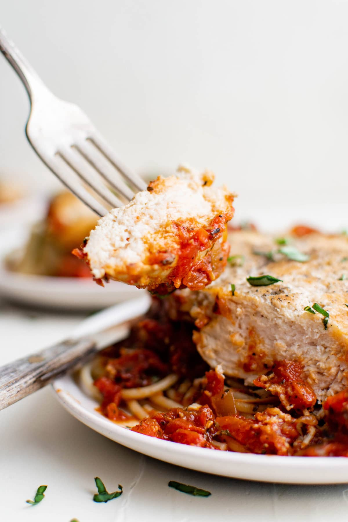 chicken breast, fork, pomodoro sauce, spaghetti, white plates