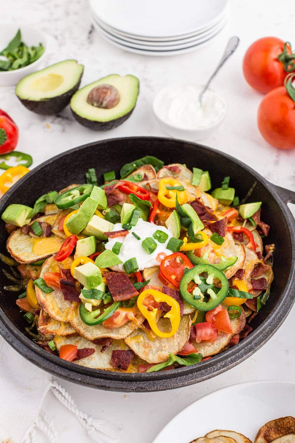Irish nachos with turkey bacon, melted cheese, green onions, and bell peppers on a black plate.
