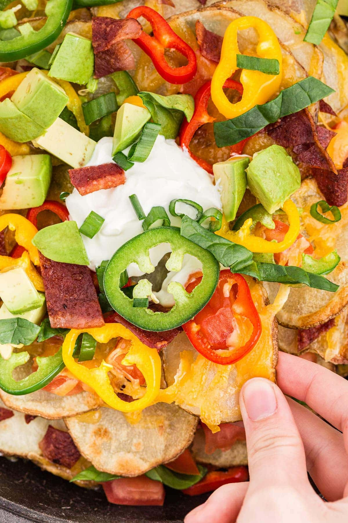 Baked Irish nachos with bell peppers, jalapenos, tomatoes, bacon, and sour cream on baked potato chips.