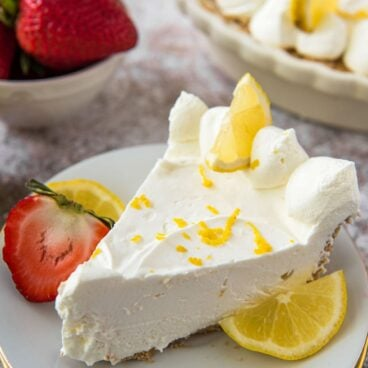 A slice of lemon cheesecake on a white plate with strawberries and lemon on the side