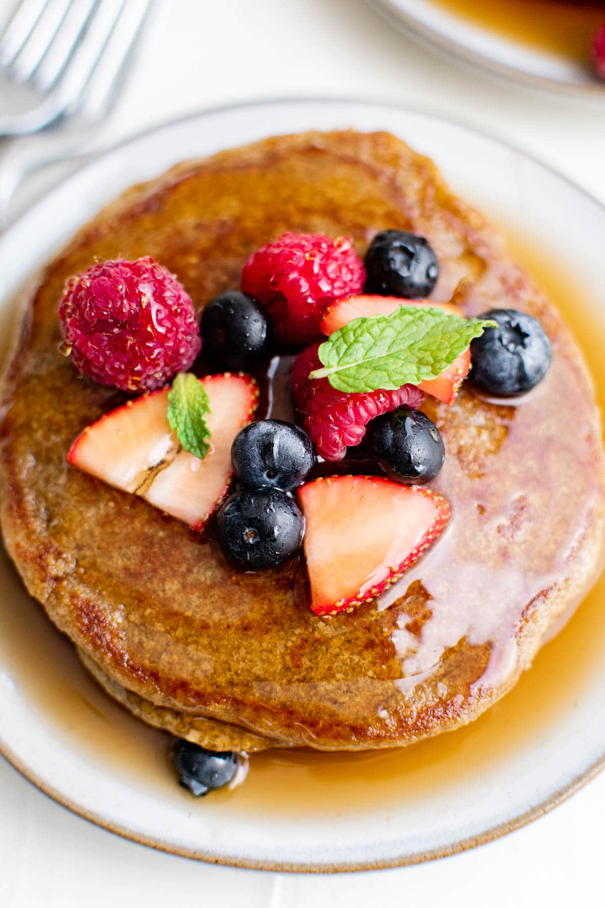 overhead image of oatmeal pancakes on a white plate with syrup and fresh berries