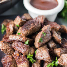 plate of steak bites topped with parsley