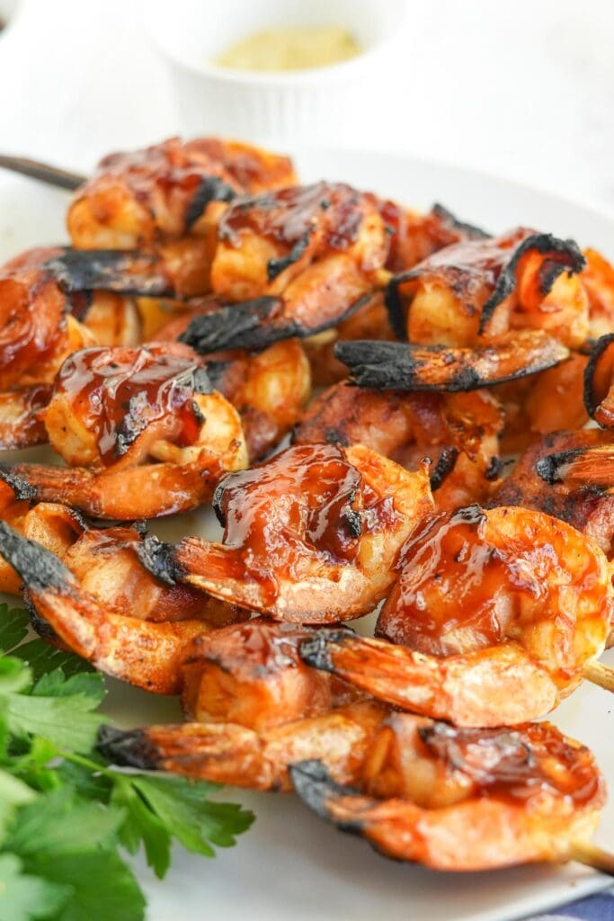 cose up of bacon wrapped shrimp with bbq sauce threaded on skewers on a white plate with parsley