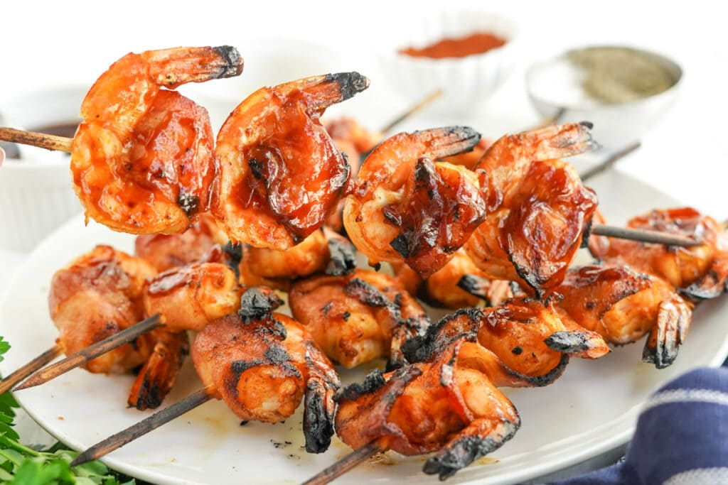 bacon wrapped shrimp on skewers with bbq saucce