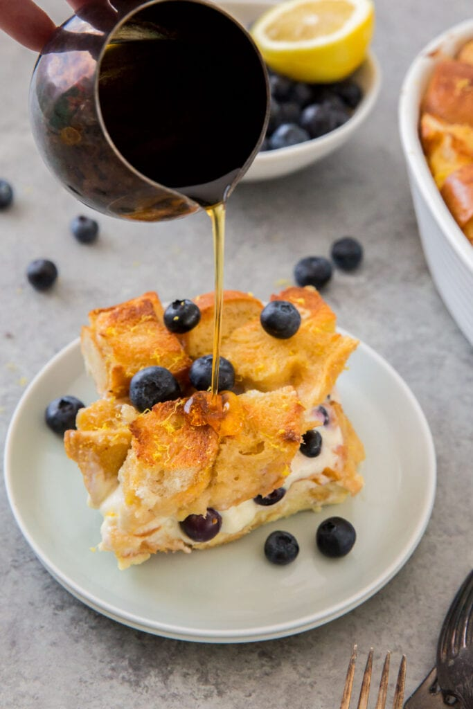 slice of blueberry french toast casserole, pitcher pouring on maple syrup