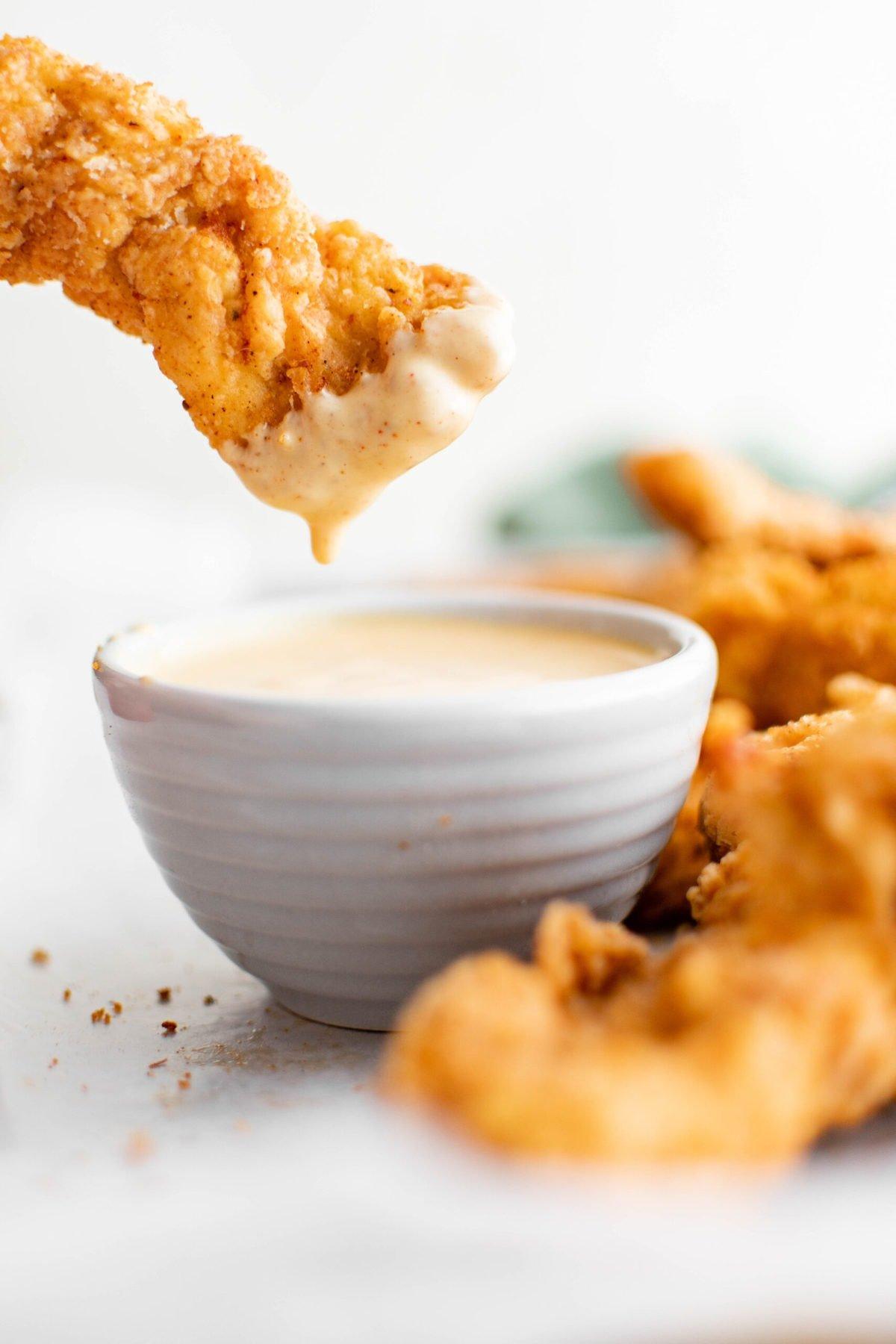 crispy chicken tenders, white dish, honey mustard dipping sauce.