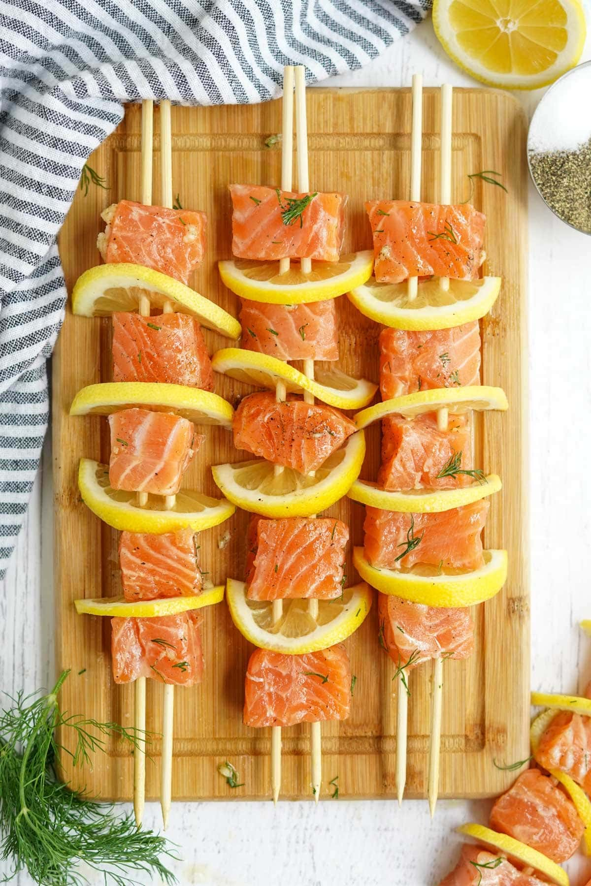 raw salmon threaded onto skeres with lemon slices and dill