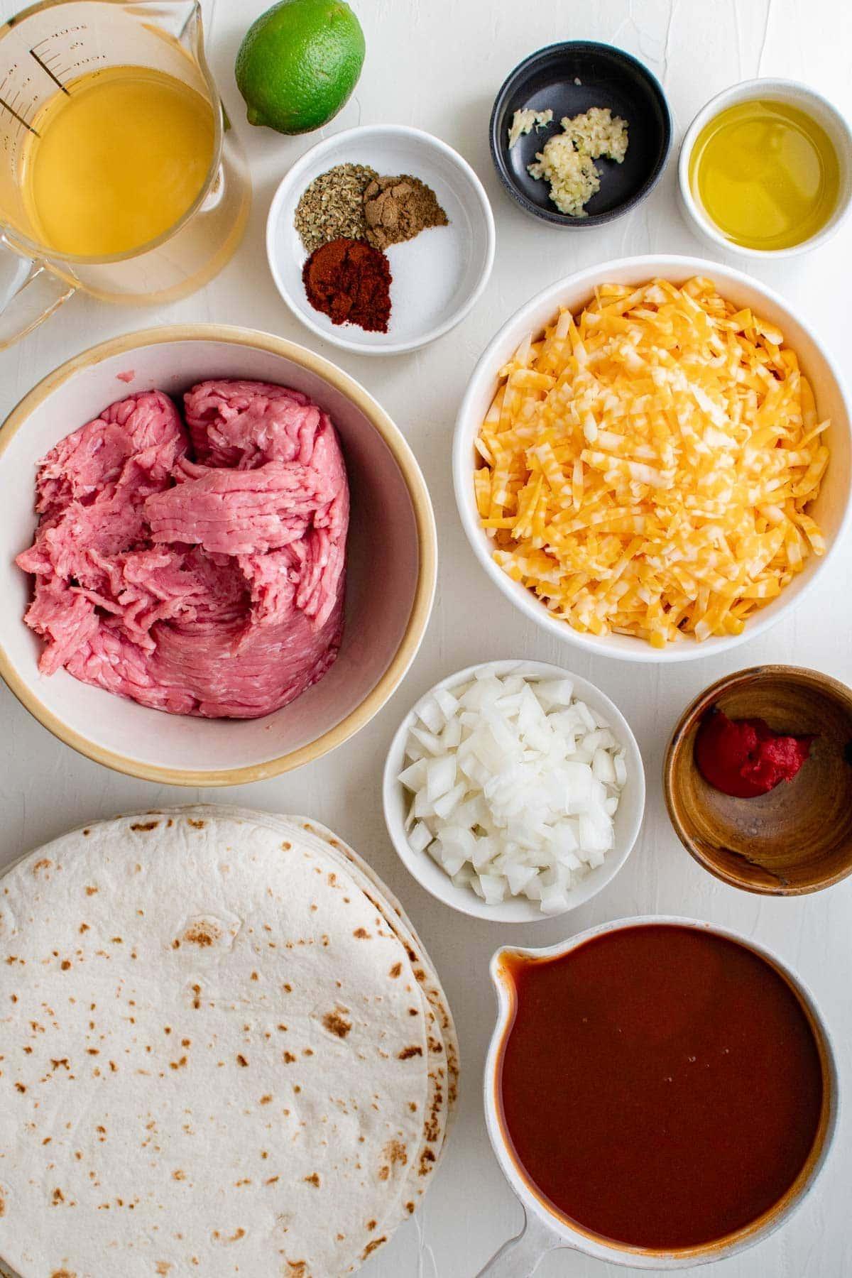 ingredients for ground turkey enchiladas in small bowls, tortillas