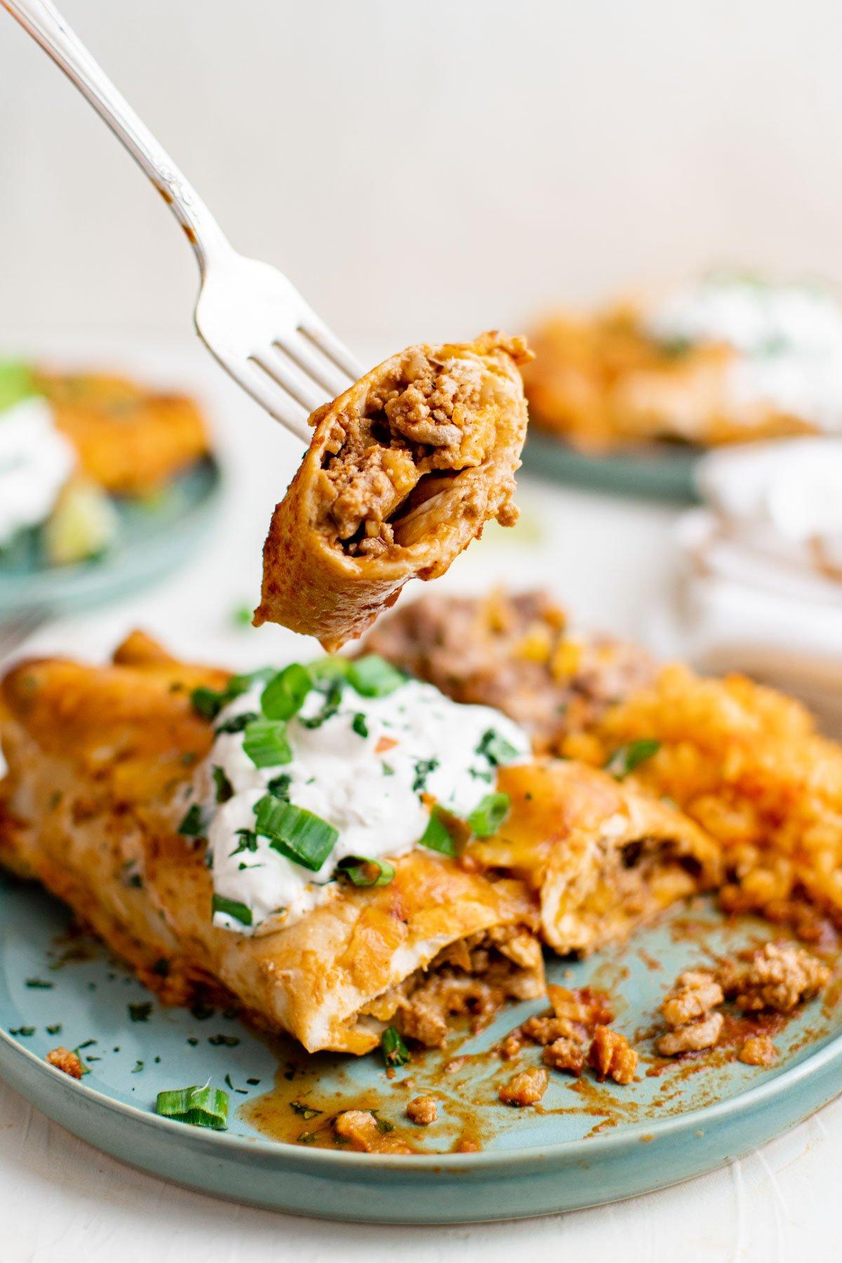 ground turkey enchiladas on a blue plate, a fork sour cream