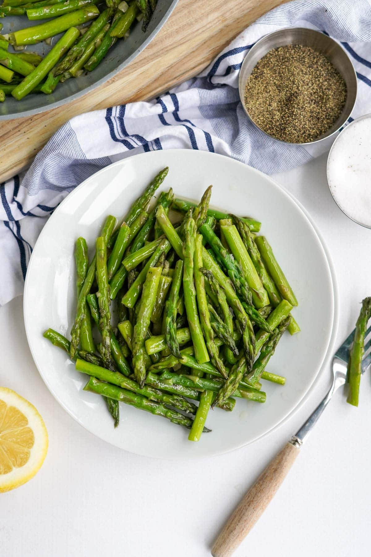 small white plate with asparagus, blue and white napkin, lemon