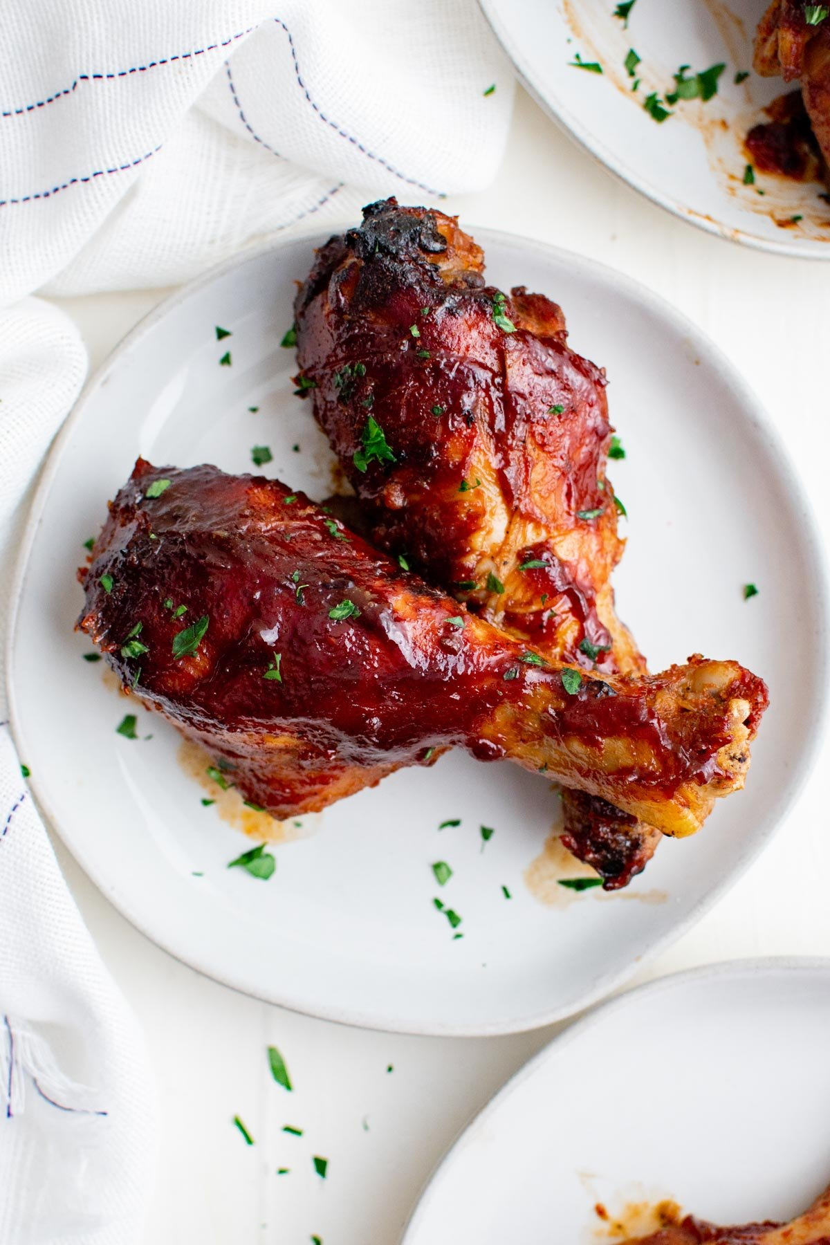 chicken legs with bbq sauce on a white plate