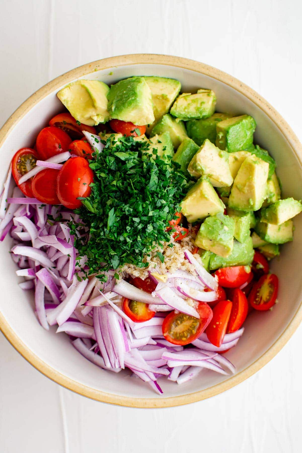 chopped avocados, tomatoes, parsley, sliced red onions in a white bowl