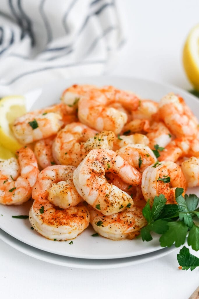 air fryer shrimp on a white plate with parsley and lemon
