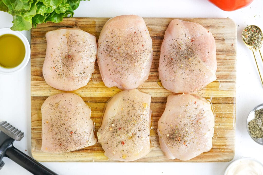 raw chicken breasts on a cutting board with seasoning