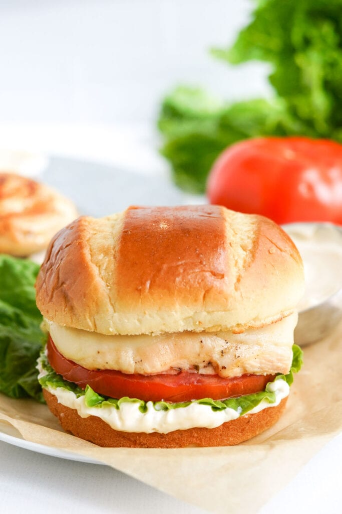 chicken sandwich on parchment paper, lettuce, tomatoes