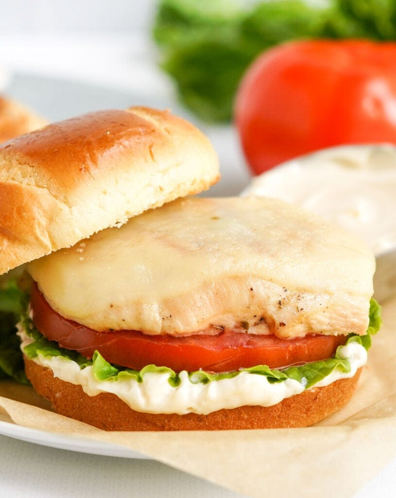 grilled chicken, tomato, lettuce, may on a brioche bun with the top half slightly off
